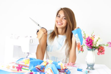 sew: Girl and a sewing machine on a light background Stock Photo