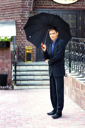 Man in black with an umbrella photo