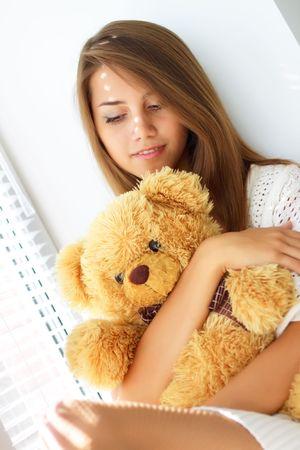 Sad girl holding a teddy bear photo