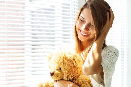 persiana: Ragazza sorridente seduto vicino alla finestra