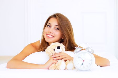 smiling girl lying on the bed with a teddy bear Stock Photo - 7706748