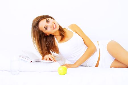 woman apple: Beautiful girl lying on the bed with a book