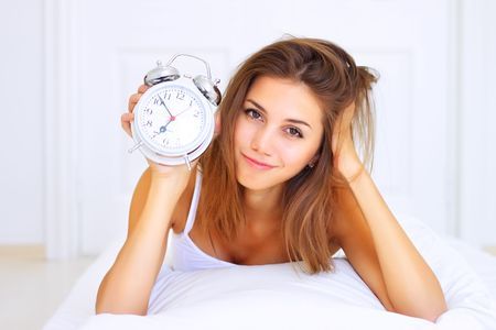 Beautiful girl lying on the bed and holding a clock photo