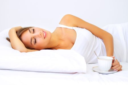 Beautiful girl sleeping on a white bed photo