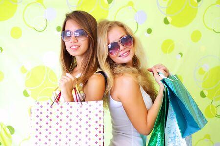 chicas de compras: Dos chicas atractivas sobre un fondo verde  Foto de archivo