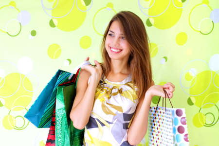 Beautiful girl with shopping bags on a green background
