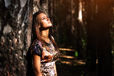 only: Dreamy girl standing next to a tree Stock Photo