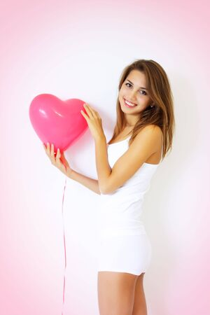smiling girl holding a large decorative heart photo