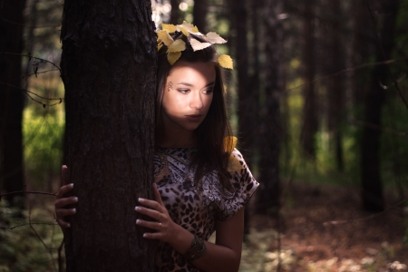 Dreamy girl standing next to a tree photo
