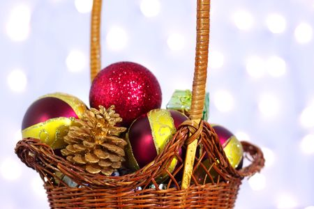 Christmas toys in a wicker basket on a background of lights photo