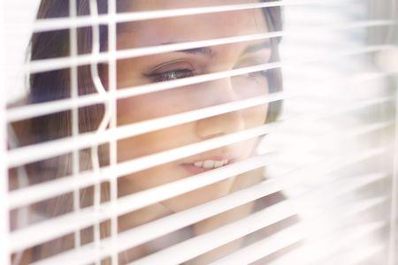 Chica atractiva mira de persianas