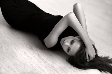 Attractive girl lying on the floor of the wood
