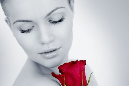 Thoughtful girl with a red rose on a gray background Stock Photo - 8193032