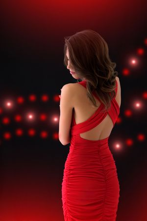 Elegant girl in a red dress on a black background with the lights photo