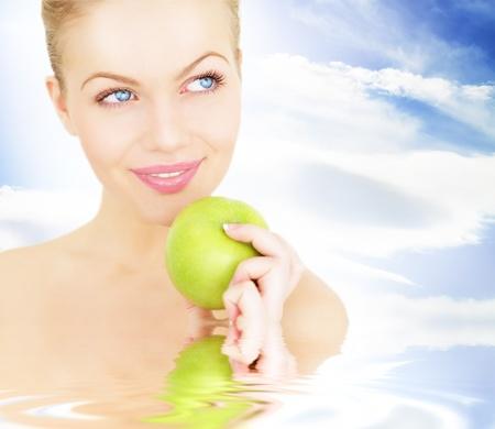 Girl against the blue sky holding an apple photo