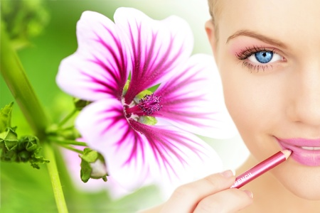 Applying lipstick using lip concealer brush against the background of a flower photo