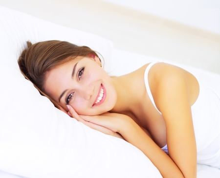 smiling girl lying on the bed photo