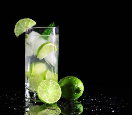Mojito cocktail with fresh limes on a black background photo