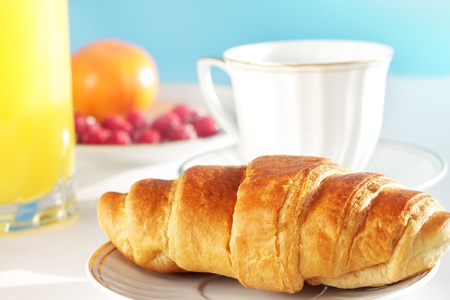 Breakfast. A cup of coffee, croissant, orange juice and berries photo