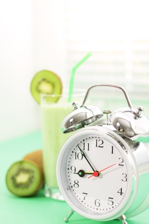 Kiwi juice in a glass and alarm clock on a light background photo