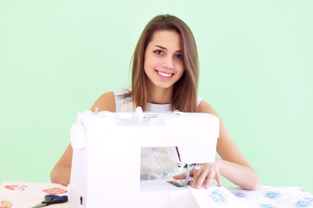 Woman using sewing machine to sew clothing Stock Photo