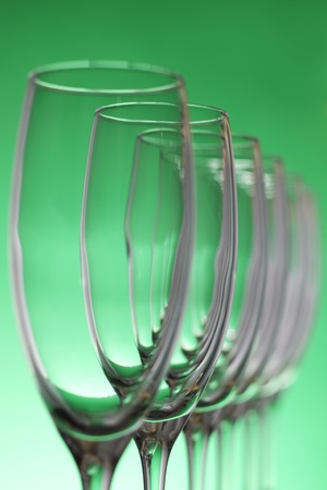 Empty champagne glasses on a green background photo