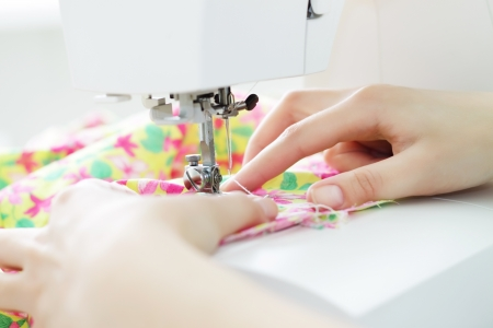 silk thread: Fabric in a sewing machine on a light background Stock Photo