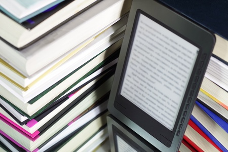 E-book reader against the background of a stack books