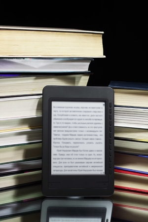 e reading: Ebook reader against the background of a stack books