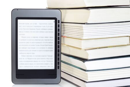 the reader: Ebook reader on pile of ordinary books