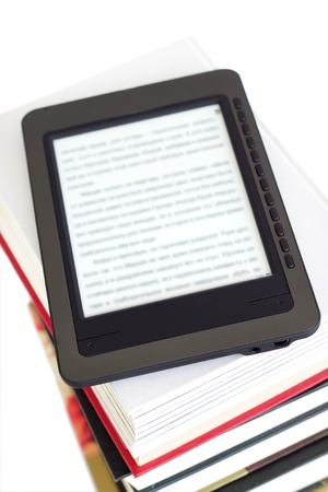 Ebook reader on pile of ordinary books photo