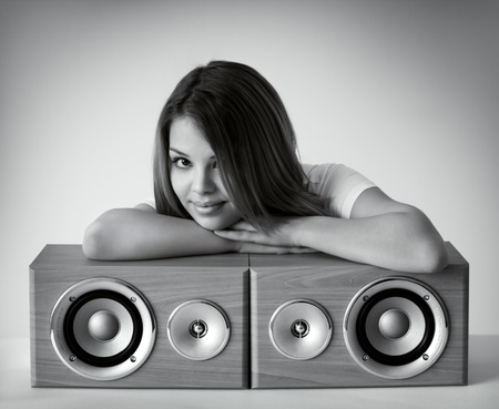 Attractive girl with loudspeakers on a gray background Stock Photo - 9124948