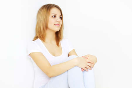 Pretty young lady sitting on the floor on light background Stock Photo - 9124937