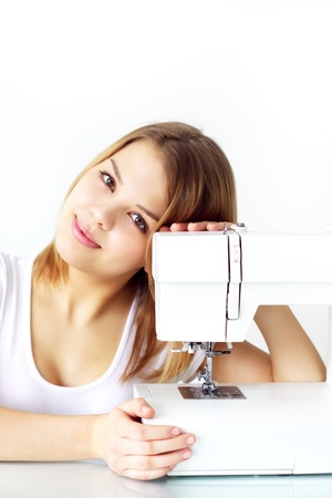 girl with sewing machine on light background photo