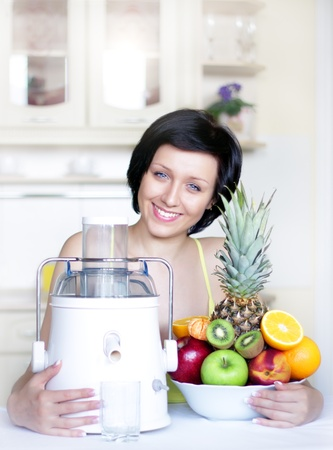 young woman with a juicer in the kitchen Stock Photo - 9230516