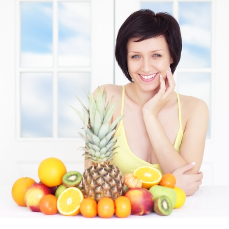 young woman with fruits on light background Stock Photo - 9230515