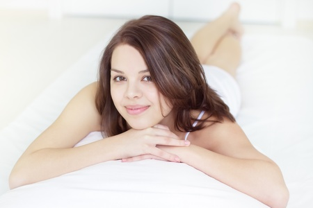 Smiling girl lying in bed on a light background photo