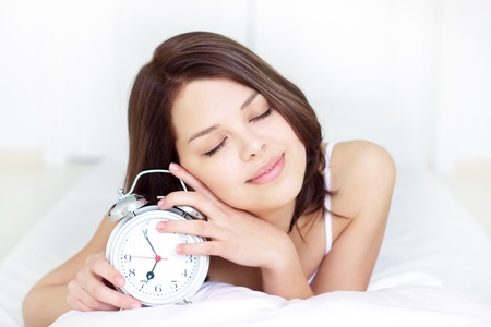 Girl with Alarm Clock on a light background photo