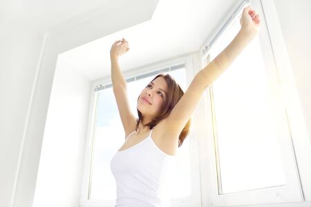 Girl stretching in the morning against the window Stock Photo - 9230524