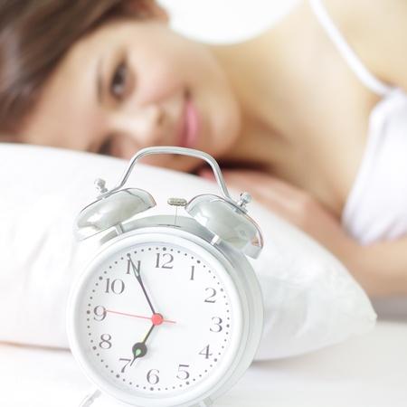 despertador: Ni�a con reloj de alarma sobre un fondo claro