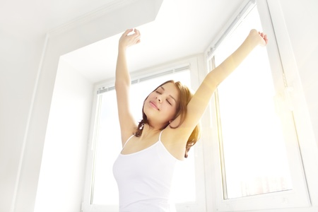 Girl stretching in the morning against the window Stock Photo - 9230657