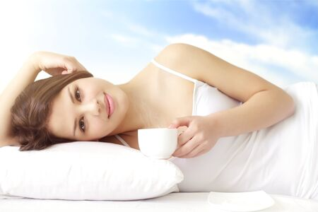 Girl with cup of coffee in bed