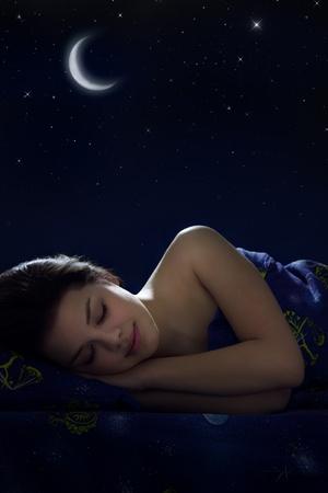 wellness sleepy: Girl sleeping at night on background of the moon Stock Photo
