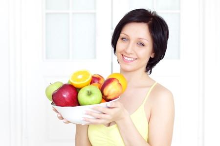 Girl holding fruit on a light background photo
