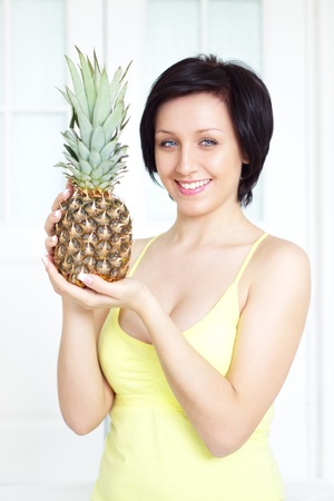 girl holding a pineapple on a light background photo