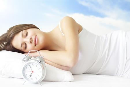 woman clock: Ni�a dormir en la cama blanca