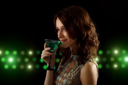 copa martini: mujer joven con un c�ctel sobre un fondo negro verde Foto de archivo