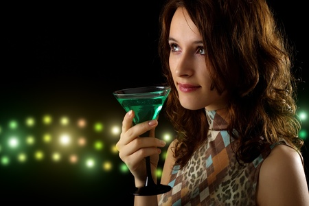 young woman with a green cocktail on a black background photo
