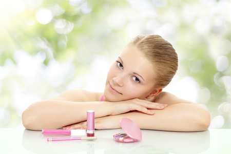 20s  closeup: Girl with cosmetics on a green background Stock Photo