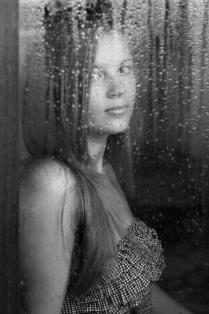 Portrait of a beautiful girl and rainy window. photo